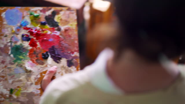 Artist holding palette and mixing colorful paint with paintbrush video