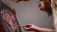 Artist painting on a canvas with brush and palette video