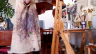 Artist painting on canvas with fine brush in her studio video