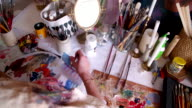 Artist painting on paper on a messy studio table video