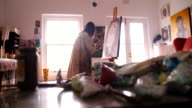 Artist painting self portrait in oil paints on a canvas video