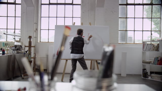Artist painting with red color on canvas video