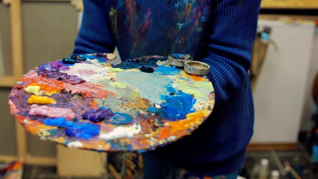 artist paints a picture of oil paint brush in hand with palette video