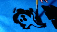 Artist paints in ink ghost for Halloween through a stencil video