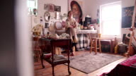 Artist smiling in her studio wearing smock and holding paintbrushes video