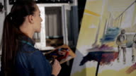 Artist working on an oil painting. View of canvas. video