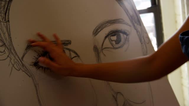 Artist working on self portrait in studio, closeup video