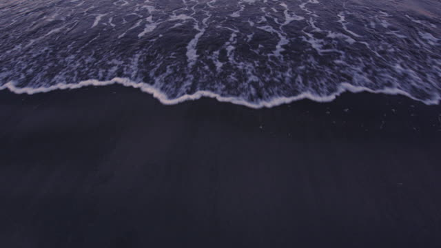 Artistic POV shot of an incoming tide on a sandy beach at sunset. Original stock color video shot in 6K by a RED Dragon camera. video