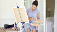 Artistic young woman working on a painting video