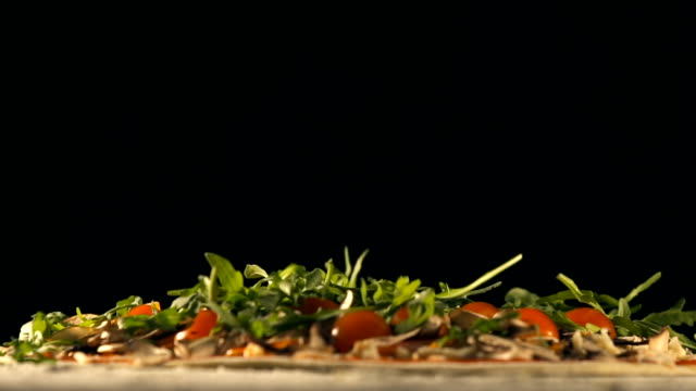 Arugula falls on pizza. Slow Motion video