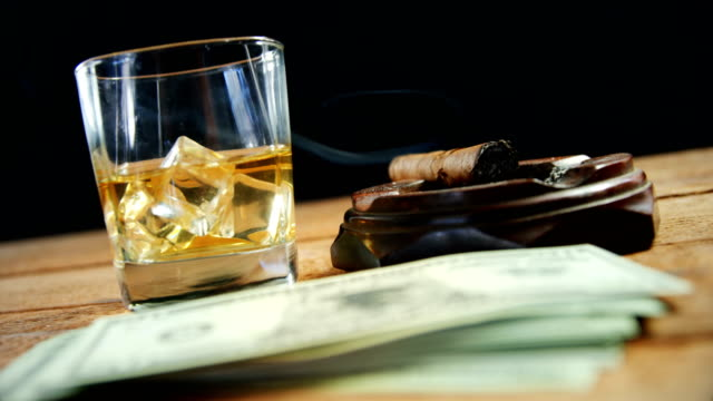 Ashtray, cigar, whisky and US dollars on table 4k video