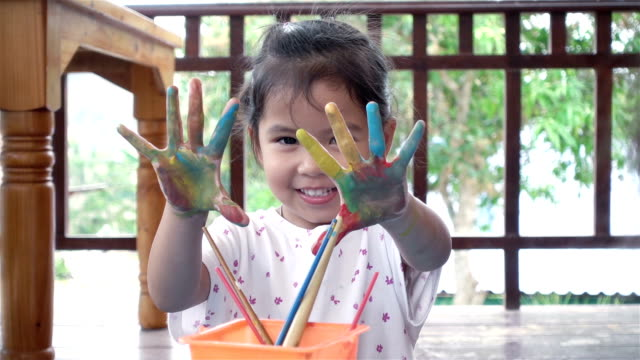 Asia children showing her hand with painting in house. Child crafts in leisure time. video