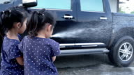 Asia little girl holding water hose and inject to wash a car video