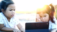 Asia little girl using pad with her sister at sunset video
