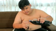 Asian fat man drinking cola in home video