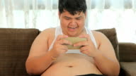 Asian fat man Relaxing in the sofa with the video