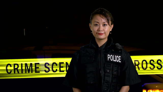 Asian American  female police officer smiling at camera with crime scene in background video