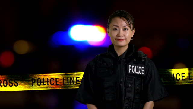 Asian American policewoman smiling at crime scene with siren in background, grunge look video