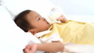 Asian baby boy drinking milk from bottle. video