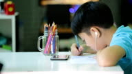 Asian boy in student uniform are painting on a white paper video