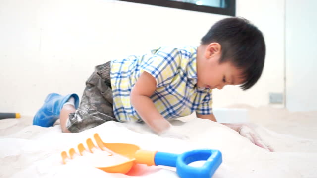 Asian boy is playing in Sandbox with colorful toys. Sand pool are good for small child development. video