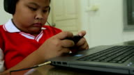 Asian boy playing game on mobile phone format VDO HD. video