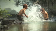 HD: Asian boys having fun playing in the river with splashing water together video