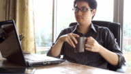 asian business man drinking coffee and looking at laptop computer video