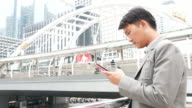 Asian business man using a tablet computer outside office video
