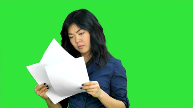 Asian business women looking document file in her hand on a Green Screen, Chroma Key video