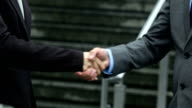 Asian businessman and businesswoman shaking hand in street video