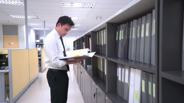 Asian businessman are searching for an information form files folders video