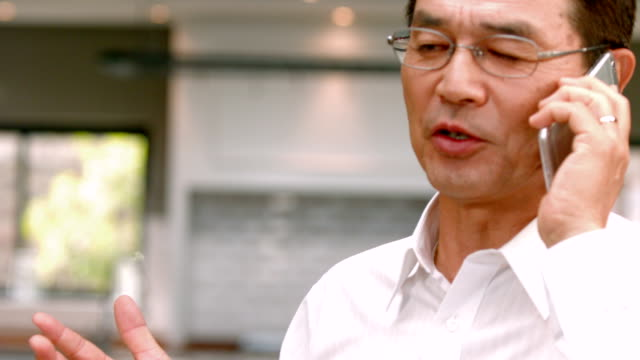 Asian businessman phoning in the kitchen video