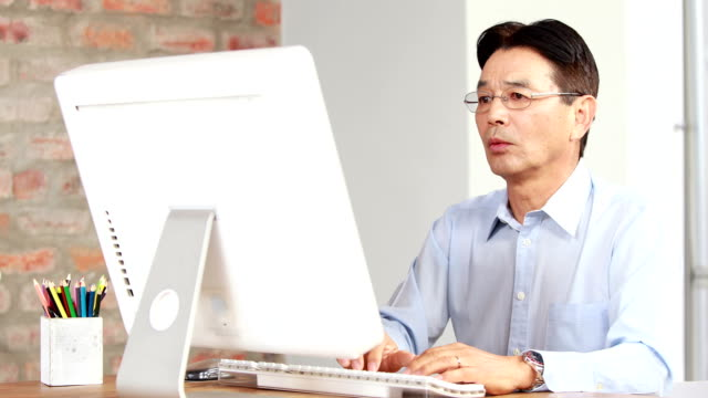 Asian businessman using computer at desk video