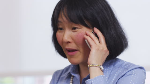 Asian businesswoman talks on cell phone video