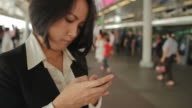 Asian businesswoman working with smartphone at train station platform video