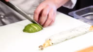 Asian chef cutting avocado for sushi rolls video