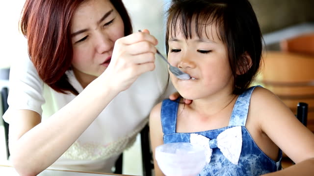 Asian child eating an ice creme with my mother in relax time . video