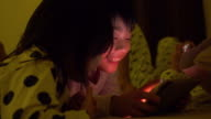 Asian child playing game on mobile phone video