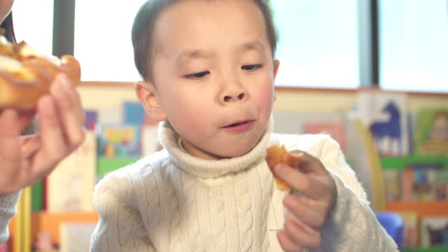 Asian children and preschool teacher eating pizza in classroom video
