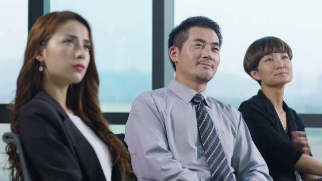 asian corporate people listening to presentation video