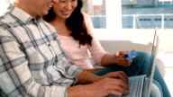 Asian couple shopping online using laptop and credit card video