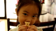 Asian cute little girl eating a biscuit video