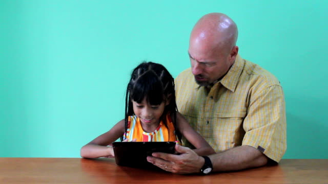 Asian Daughter Showing Dad Tricks On Digital Tablet video