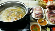Asian eating thai food.fish meat in a Pan of Hot Water video