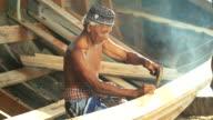 Asian elderly carpenter making wooden boat. video