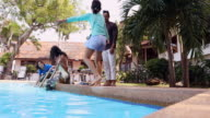 Asian Family on Vacation Splashing at a Resort Pool video
