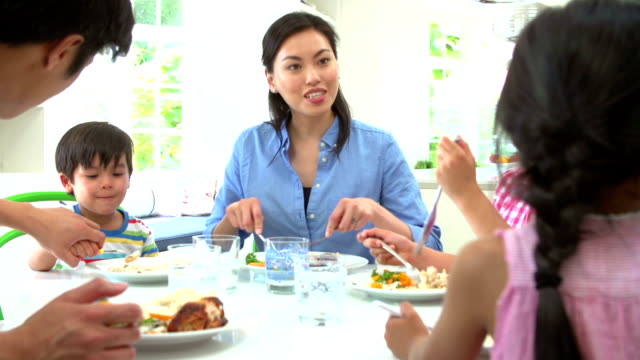Asian Family Sitting At Table Eating Meal Together video