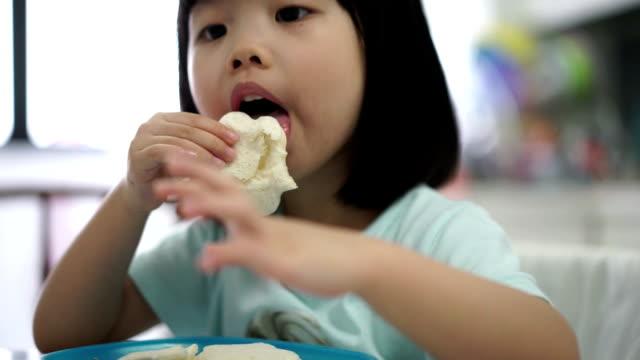 Asian female child enjoying her breakfast video