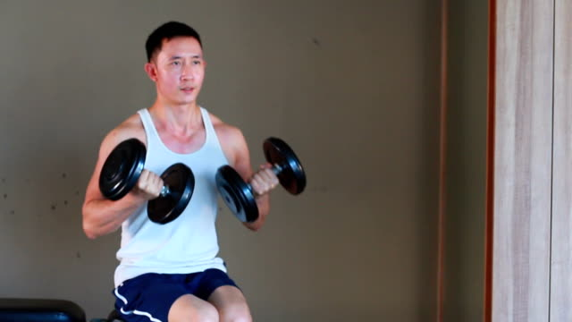 Asian fitness man does dumbbell curl exercises  in the gym video